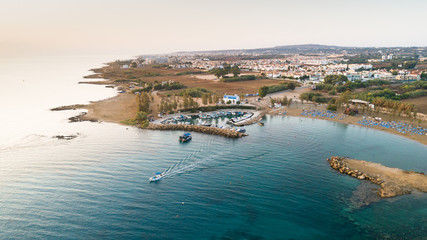 Aerial bird's eye view of coastline sunset, landmark white washed chapel Agia Triada beach, Protaras, Famagusta, Cyprus from above. Ayia Trias bay church and a boat out of the small port at sunrise.