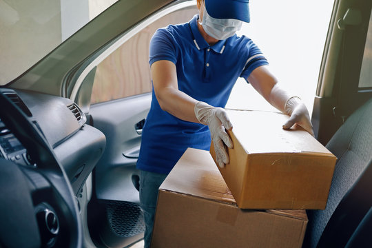 Delivery services courier during the Coronavirus (COVID-19) pandemic, courier wearing medical mask and latex gloves working with cardboard boxes on van seat.