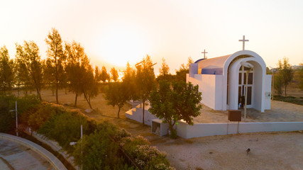 Aerial view of sunset and landmark white washed seaside modern arch chapel of Agia Triada, Protaras, Famagusta, Cyprus from above. Tourist attraction Ayia Trias blue bay church by the beach at sunrise