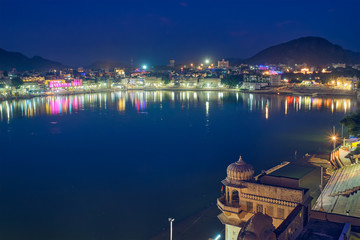 Wall Mural - Night view of famous indian hinduism pilgrimage town sacred holy hindu religious city Pushkar with Brahma temple, aarti ceremony, lake and ghats illuminated. Rajasthan, India. Horizontal pan