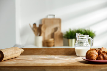 Fototapete - Wooden table in a sunny kitchen in the morning light during breakfast