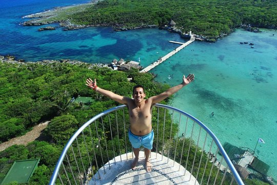 High Angle Portrait Of Shirtless Man With Arms Outstretched At Balcony Against Sea