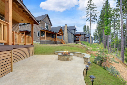 Beautiful wooden back porch with chairs on the hill and large backyard patio with fire pit and pine trees.