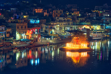 Fotomurales - View of famous indian hinduism pilgrimage town sacred holy hindu religious city Pushkar with Brahma temple, aarti ceremony, lake and ghats illuminated at sunset. Rajasthan, India. Horizontal pan