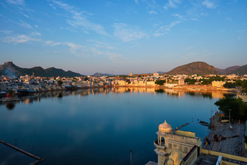 Wall Mural - View of famous indian hinduism pilgrimage town sacred holy hindu religious city Pushkar amongst hills with Brahma mandir temple, lake and traditional Pushkar ghats at dusk sunset. Rajasthan, India