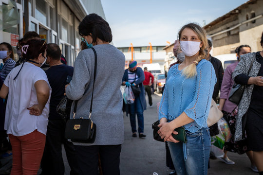 young woman standing in line at the market. in a protective mask during a coronovirus pandemic. dressed in a blue sweater and jeans. blonde with gathered hair. Coronavirus pandemic effects.