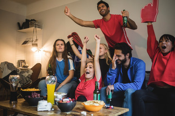 Multi-ethnic friends watching sport while sitting on sofa at home