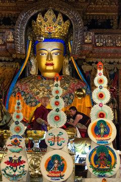Monks stand before a Golden Buddha statue in Pelkor Chode Monastery in Tibet.