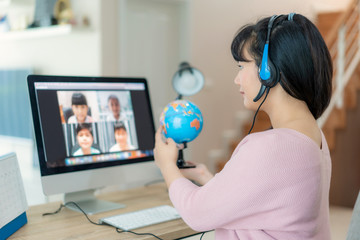 Obraz Asian woman teacher teaching geography via video conference e-learning and cheerful elementary school student looking at globe, Homeschooling and distance learning ,online ,education and internet.. - fototapety do salonu