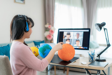 Asian woman teacher teaching solar system via video conference e-learning and cheerful elementary school student looking at globe, Homeschooling and distance learning ,online ,education and internet..