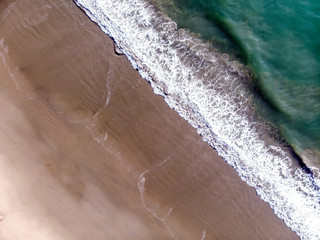 Aerial view of beach, looking down on emerald green Pacific Ocean waves washing up on sandy California beach. Drone photography