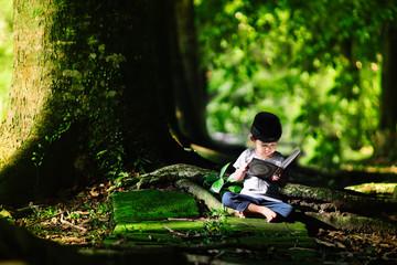 Boy Reading Koran While Sitting Against Trees