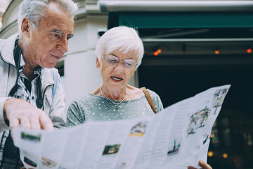 Senior woman reading map while standing with partner in city during vacation