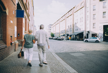 Rear view of senior couple walking on sidewalk in city during vacation