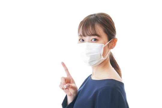 マスクを装着して指を指す若い女性