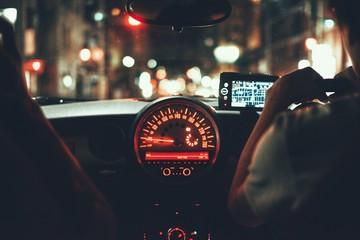 Rear View Of Man Driving Car At Night