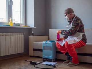 elderly man in special clothes, glasses and apron pours poisonous substance into container of sprayer. Two component poison against bed bugs. Military pensioner ready to fight insects