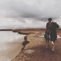 Portrait Of Man Riding Horse By Lake Against Sky