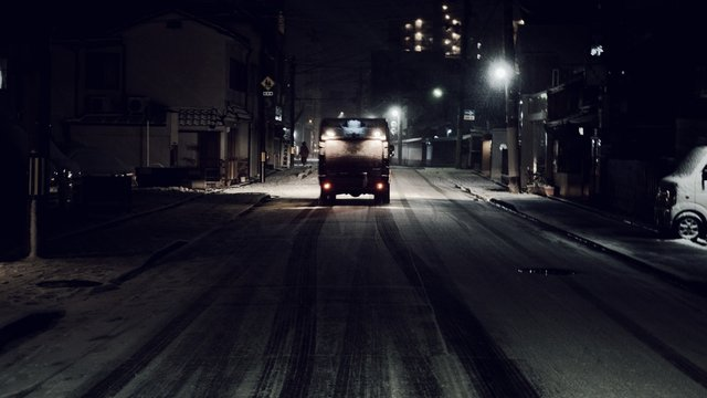 Garbage Truck On Snow Covered Street At Night