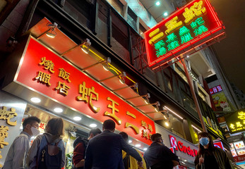 People wearing face masks line up outside a snake restaurant in Hong Kong