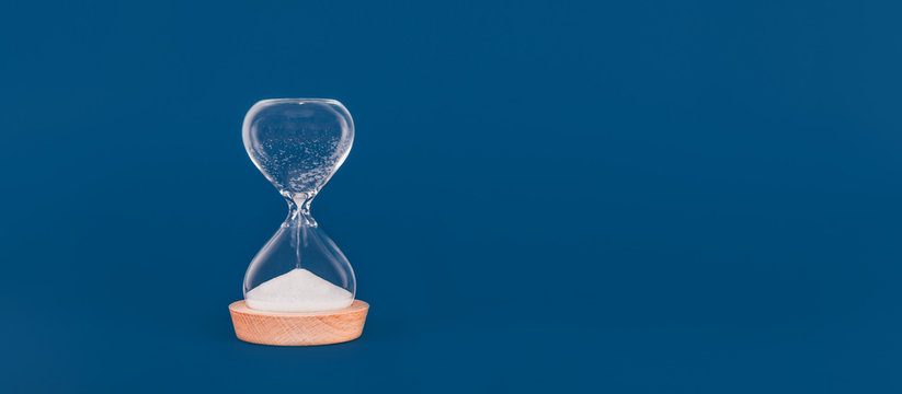 Hourglass with the last drops of sand. Concept of time and timely actions, closing opportunities. Wide screen banner format with place for text