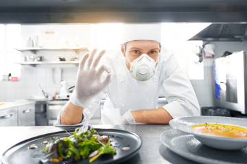 health, safety and pandemic concept - male chef cook wearing face protective mask or respirator for...