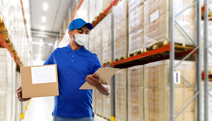 Wall Mural - health, safety and pandemic concept - happy indian delivery man wearing face protective medical mask for protection from virus disease with parcel box and clipboard in uniform over grey background