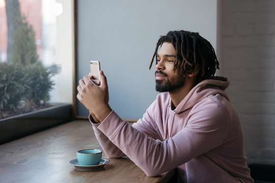 Handsome African American man using mobile phone, communication, sitting in cafe. Successful freelancer working from home