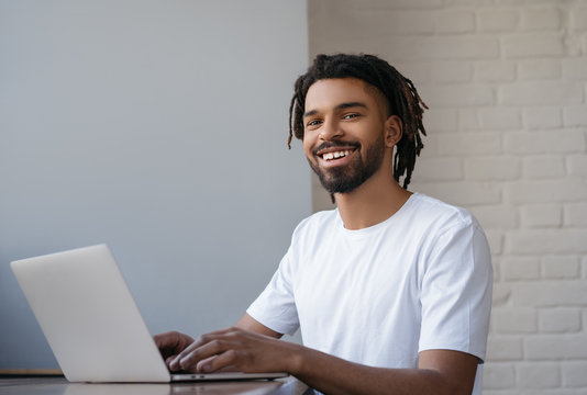 African American freelancer working from home. Portrait of young successful programmer using laptop computer, looking at camera and smiling, sitting at workplace