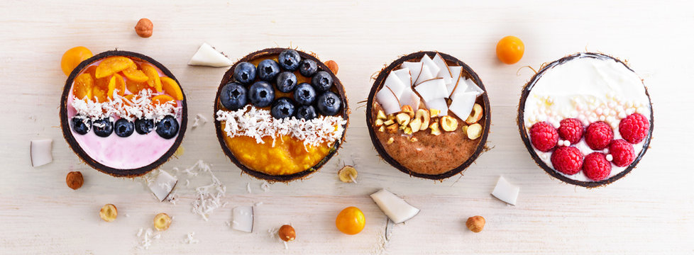 top view four colorful smoothie bowls with blueberries, raspberries, physalis and coconut shavings in coconut bowls on white background