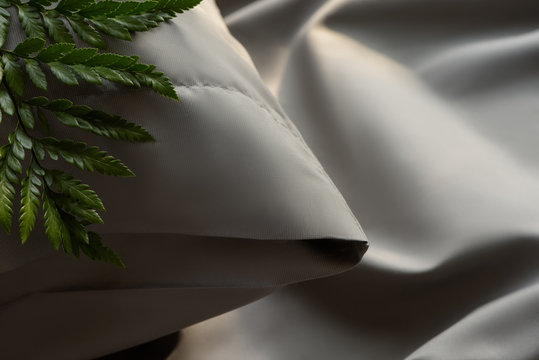 bed linen in gray,  silk fabric texture, green leaf on the bed