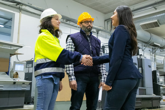 Positive businesswoman and engineers meeting onsite and shaking hands. Man and woman in hardhat, uniform and business suit standing on plant floor. Business and industry concept