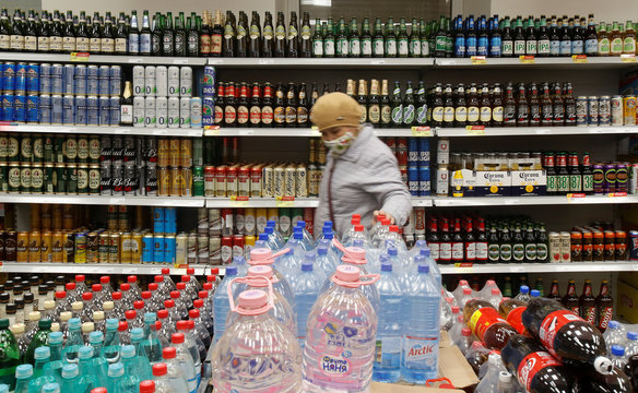 A customer walks past shelves with bottles and cans of beer in a supermarket in Moscow