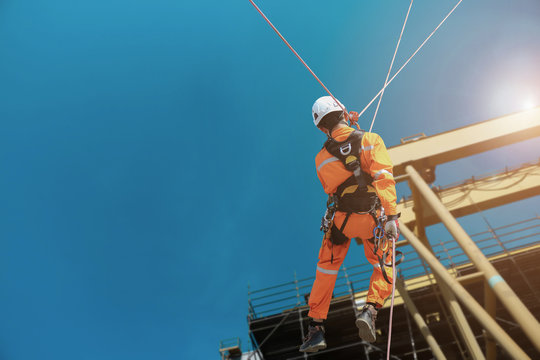 Rope access Safety sprinkling worker on high with scaffolding wearing dresses and safety man with full harness safety concept in site construction building on tower crane background.