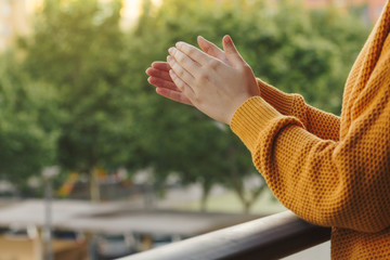 Stock photo of a hands of a young woman clapping from the balcony to support the medical team
