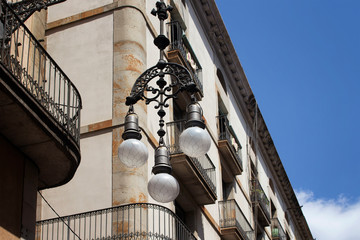 Fotomurales - Bottom view of old, traditional, ornamental street lamp with historical building in the background. It is a sunny summer day.