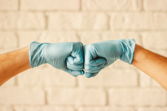 Two men bumping hands in blue medical gloves as protection against coronavirus. Doctor surgeons in blue protective latex gloves clapping fists. COVID-19 protection, new greeting, social distancing