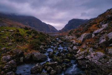 Wall Murals Deep brown Scenic view of Dunloe Gap in dusk, with mountain slopes, lake and mountain stream, Kerry mountains, Ireland