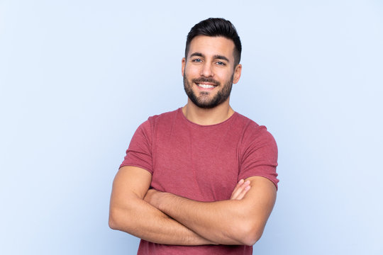 Young handsome man with beard over isolated blue background keeping the arms crossed in frontal position