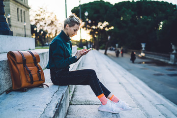 Young modern woman surfing mobile on street Fototapete