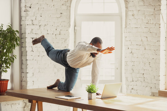 Young african-american man doing yoga at home while being quarantine and freelance online working. Remote, isolated or alone at office. Concept of healthy lifestyle, wellness, activity, movement.