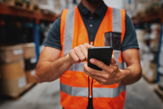 Closeup of man hands using mobile phone while in warehouse in uniform