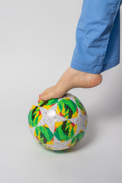 Naked female foot with a green multi-colored soccer ball.