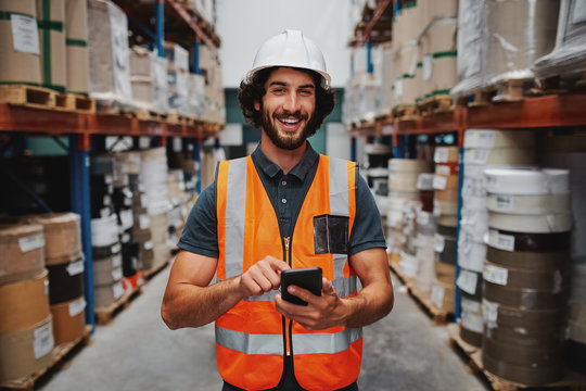 Young smiling male worker in warehouse wearing safety helmet and vest standing between shelf with goods using cellphone