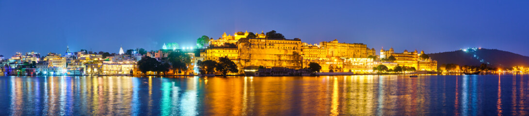 Wall Mural - Panorama of famous romantic luxury Rajasthan indian tourist landmark - Udaipur City Palace in the evening twilight with dramatic sky - panoramic view. Udaipur, Rajasthan, India