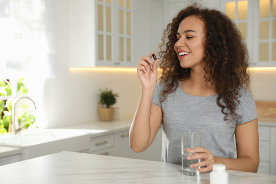 African-American woman with glass of water taking vitamin capsule in kitchen. Space for text