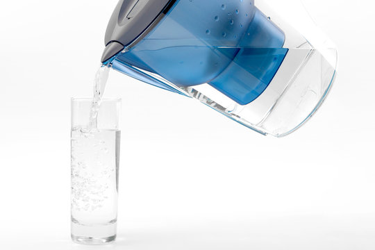 Cleanse toxins and harmful metals, purity  and tap water purification system  concept with  transparent filtration jug or pitcher pouring into a glass isolated on white background with clipping path