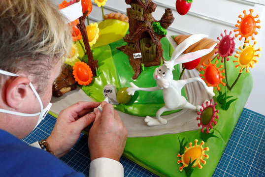 Cake maker Lewis-Anderson puts the finishing touches to a scene with chocolate tree and Easter eggs in La Hulpe