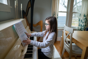 Young girl wearing glasses and turning the page of her  music book while practicing the piano at home