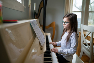 Young girl wearing glasses while reading music and practicing the piano at home